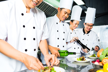 Asian Indonesian chef along with other cooks in restaurant or hotel commercial kitchen cooking, finishing dish or plate photo