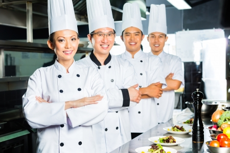 Asian Indonesian and Chinese chefs along with other cooks in restaurant or hotel commercial kitchen cooking, finishing dish or plate Imagens