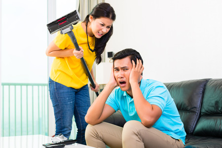 difficulties: Young Asian handsome couple having relationship difficulties with household tasks like vacuum and playing games on couch Stock Photo