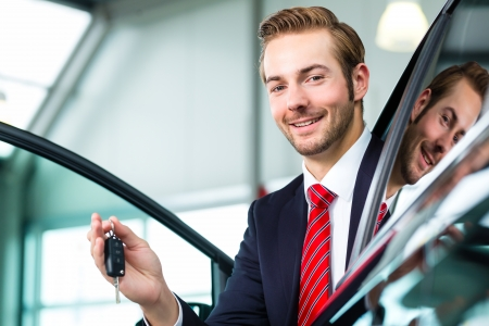 used: Seller or car salesman in car dealership with key presenting his new and used cars in the showroom