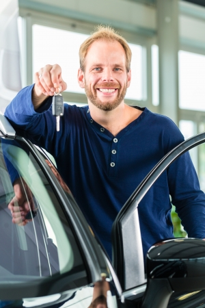 test drive: Young man beside a new car in car dealership, obviously he is buying the auto, or making a test drive and holding the keys in hand