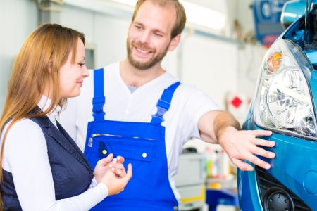 inspect: Female customer and mechanic in workshop or MOT with car for service inspection