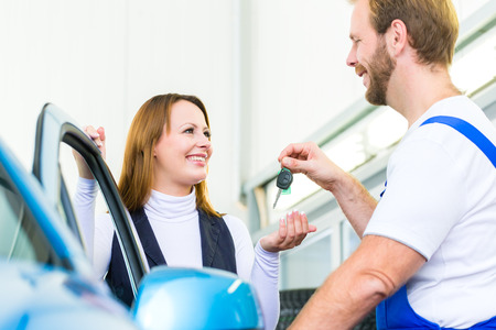 Female client and mechanic in auto workshop or MOT with car for service inspection Stock Photo