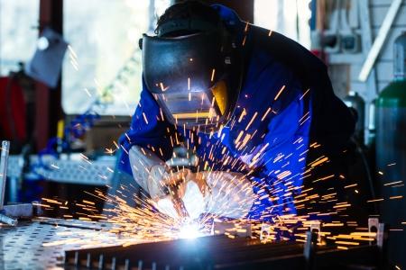 soldador: Soldador de metal pegado con el dispositivo de soldadura en el taller, un montón de chispas para ser visto, lleva gafas de soldadura Foto de archivo