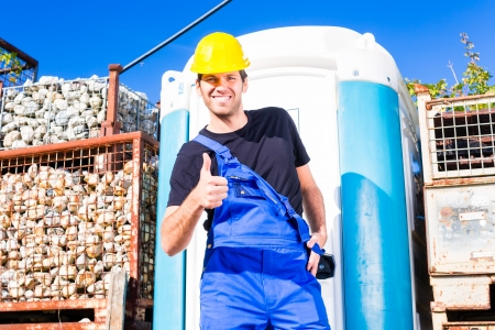 builder using mobile restroom or chemical toilet on construction or building site photo
