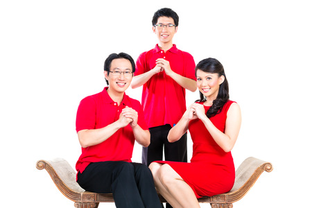 family celebrates Chinese new year traditional greeting, wearing red shirts photo