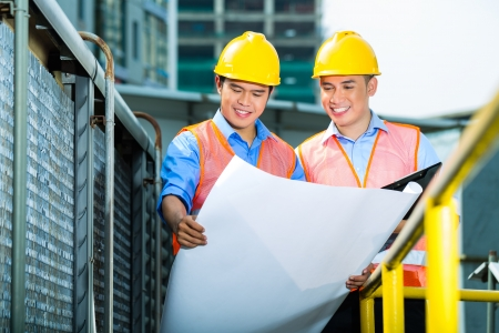 asian architect: Asian Indonesian construction workers with blueprint or plan on building site Stock Photo