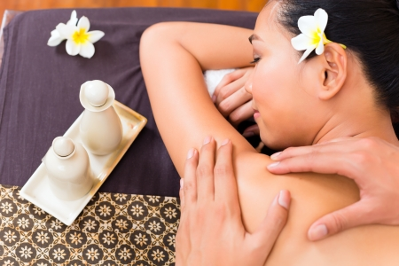 Masseur giving Indonesian Asian woman a aroma therapy massage with essential oil in a beauty wellness spa photo