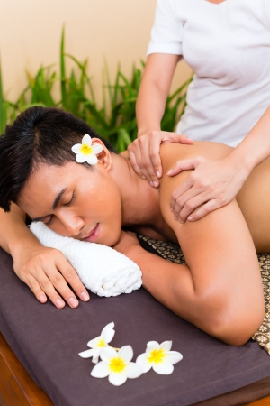 beauty parlor: Indonesian Asian man in wellness beauty spa having aroma therapy massage with essential oil, looking relaxed