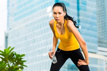 indonesian woman: Deportes urbanos - mujer indonesia asi�tica haciendo gimnasio en la ciudad en un hermoso d�a de verano Foto de archivo