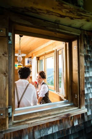 trachten: Couple in a traditional mountain hut having a meal - view through the window