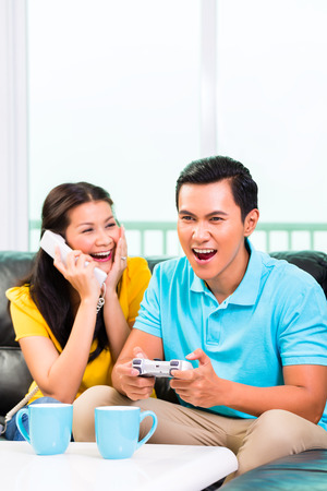 Young Asian handsome couple having leisure time together and playing with laptop video game console and phone on couch photo