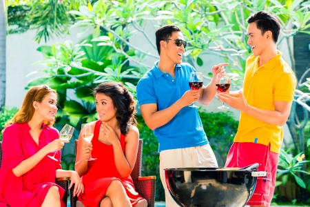 pool party: Asian friends having barbecue or BBQ at pool, drinking  wine and celebrating summer time Stock Photo