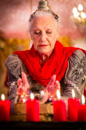interpret: Female Fortuneteller or esoteric Oracle, sees in the future by looking into their crystal ball during a Seance to interpret them and to answer questions Stock Photo