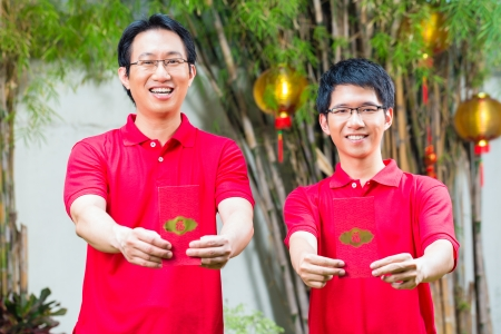 Father and grown up son celebrating Chinese new year with traditional gift, wearing red shirts Stock Photo