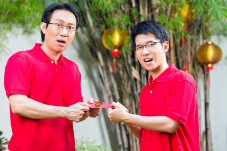 Father and grown up son celebrating Chinese new year with traditional gift, wearing red shirts photo