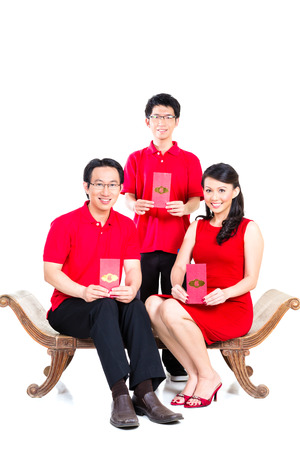 envelop: Couple celebrate Chinese new year with traditional money gift envelop, wearing red