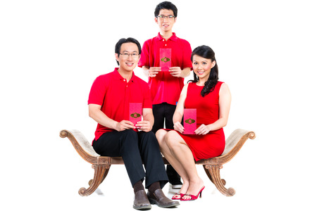 Couple celebrate Chinese new year with traditional money gift envelop, wearing red Stock Photo - 25303454
