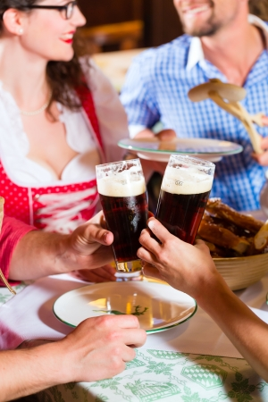 Young people in traditional Bavarian Tracht eating with sausages in restaurant or pub lunch or dinner Stock Photo - 25303516
