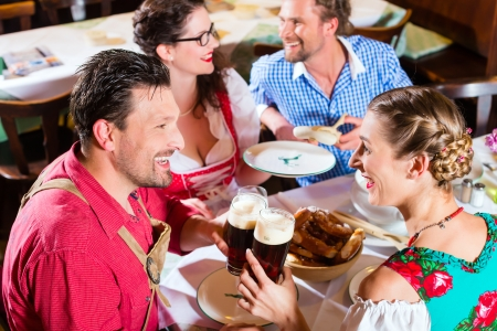 veal sausage: Young people in traditional Bavarian Tracht eating with sausages in restaurant or pub lunch or dinner