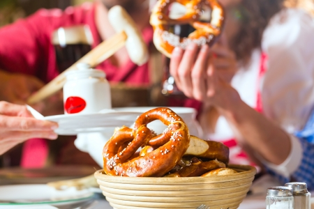 Young people in traditional Bavarian Tracht eating with sausages in restaurant or pub lunch or dinner photo