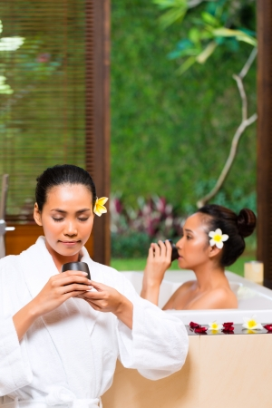 bathe mug: Indonesian Asian women in wellness beauty day spa having aroma therapy bath and drinking herbal tea for detox