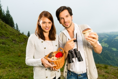 Mushrooms - young couple looking and searching for porcini in the mountains photo