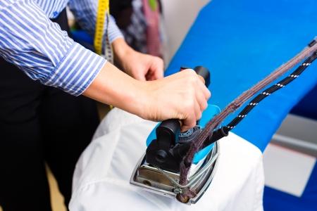 Vrouw schoner in wasserij winkel of textiel stomerij strijken jasje met de hand met ijzeren Stockfoto