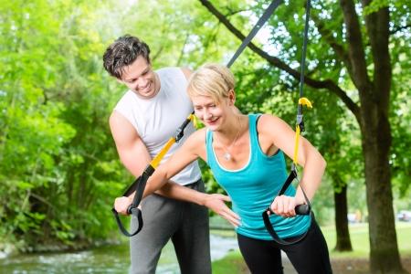 trees  summer: Mujer de la aptitud que ejercita con el entrenador de suspensi�n y entrenador deportivo personal en City Park bajo los �rboles de verano