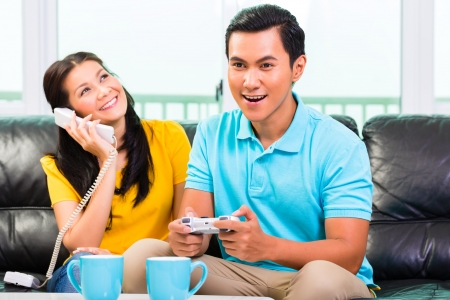 indonesia people: Young Asian handsome couple having leisure time together and playing with laptop video game console and phone on couch Stock Photo