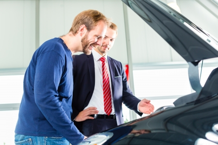 Seller or car salesman and client or customer in car dealership presenting the engine performance of new and used cars in the showroom, the men looking under the hood photo