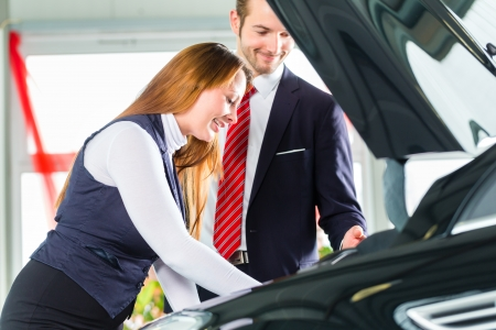 Seller or car salesman and female client or customer in car dealership presenting the engine performance of new and used cars in the showroom, the woman looks under the hood photo