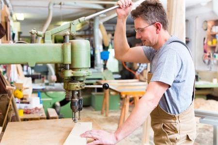 Carpenter werken aan een elektrische bankje boor, boren van een aantal planken Stockfoto