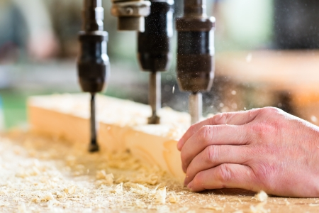 Carpenter working on an electric bench drill, drilling some boards photo
