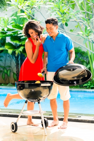 Asian handsome couple having barbecue party or BBQ outside at the pool with grilled corn cobs photo