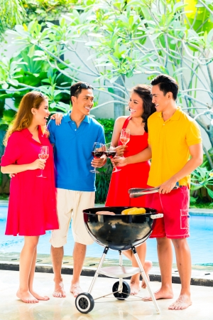 Asian friends having barbecue or BBQ at pool, drinking  wine and celebrating summer time photo