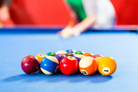 billiard balls: Couple or friends playing billiard with queue and balls on pool table  Stock Photo