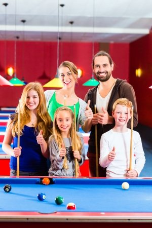 family time: Family playing together billiard with queue and balls on pool table  Stock Photo
