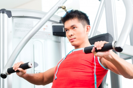 weight machine: Asian Chinese man having fitness training or workout in gym doing sport to build up muscle on a weight machine