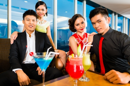 Young and handsome Asian Chinese people drinking cocktails in a luxurious and fancy lounge bar drinking cocktails  photo