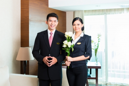 Hotel Manager or director and supervisor welcome arriving VIP guests with roses on arrival in luxury or grand hotel Stock Photo