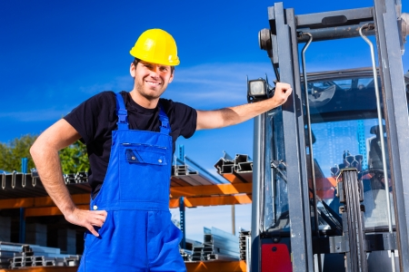 transporter: builder or driver with pallet transporter or lift fork truck on construction or building site