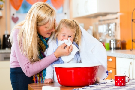 inhale: Mother care for sick child with vapor-bath at domestic kitchen  Stock Photo