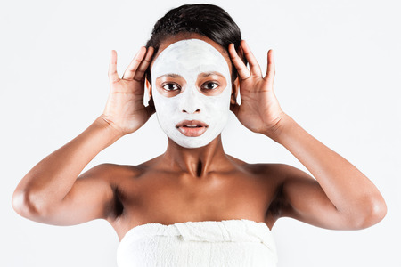 Young African woman in Studio doing body care with refreshing facial mask for young and beautiful skin and relaxation photo