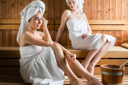 Two Women in wellness spa relaxing in wooden sauna Stock Photo - 25489407