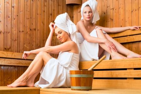 Two Women in sauna of wellness spa relaxing , enjoying an infusion Stock Photo - 25489405