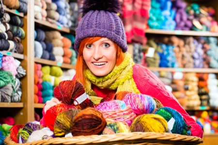 haberdashery: Young woman buying colorful wool and yarn for their hobby in a knitting shop Stock Photo