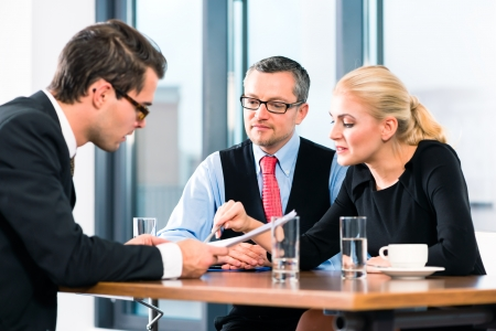 interview job: De negocios - hombre joven en una entrevista de trabajo, firma su contrato de trabajo con el jefe y su asistente femenina en su oficina Foto de archivo