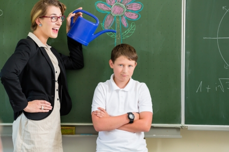 Teacher motivating school student in front of the board Stock Photo
