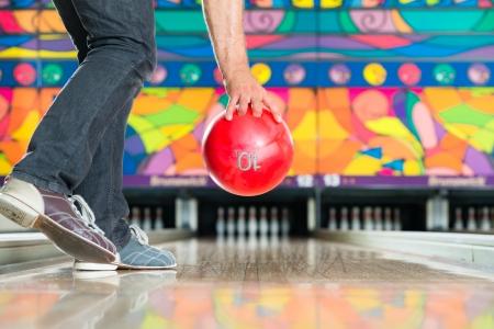 speld: Jonge man in een bowlingbaan plezier, de sportieve man die een bowling bal voor de tien pin steegje